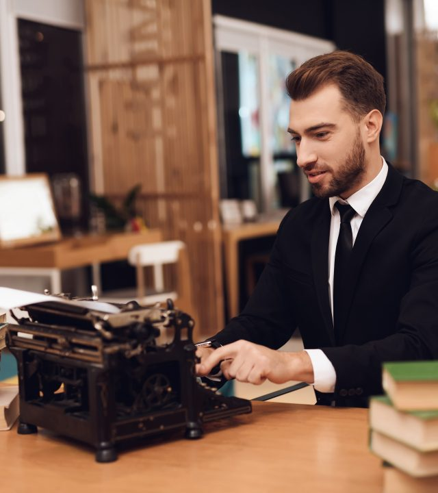 Man in suit is sitting at table with an old typewriter.